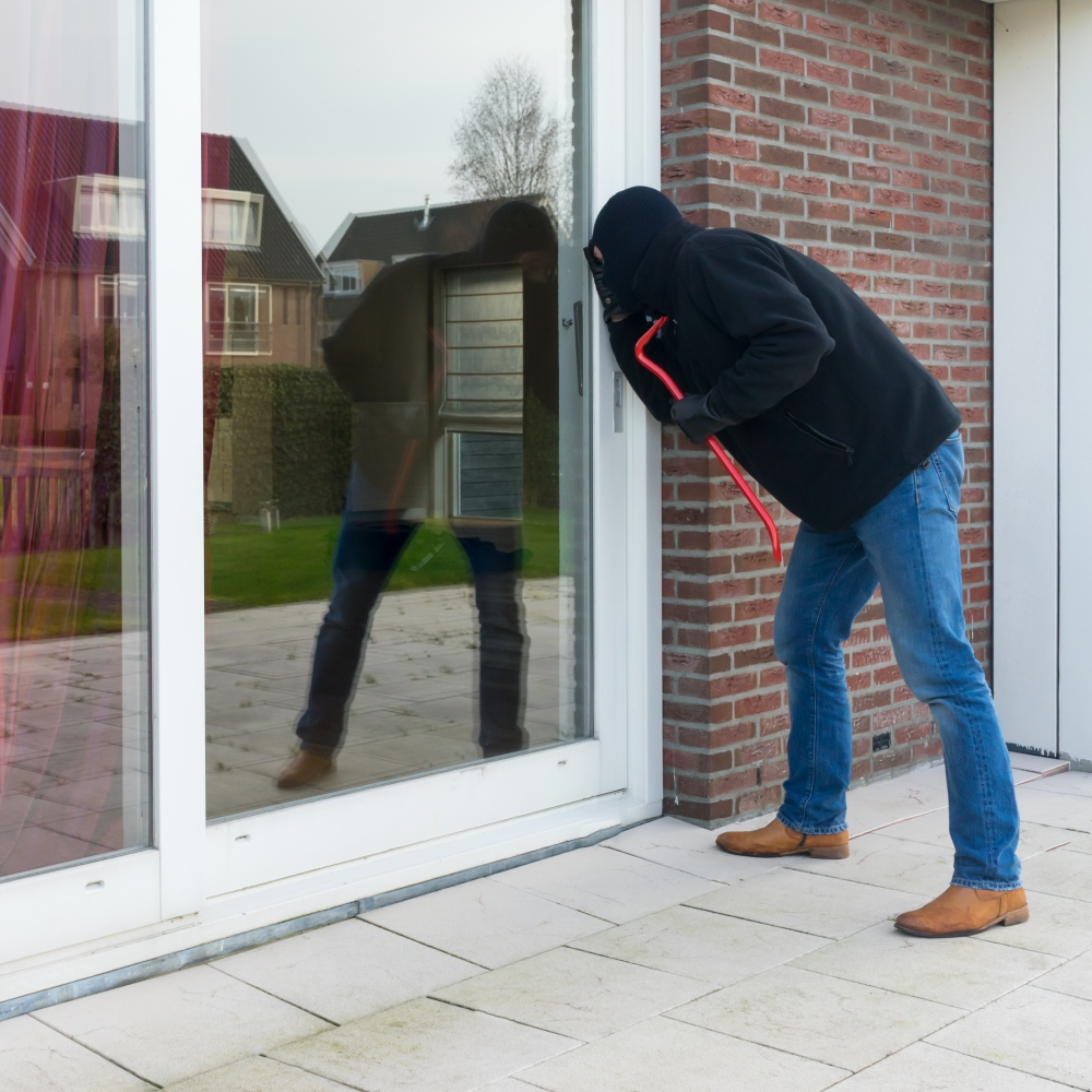 Burglar looking through window of house, while owners are on summer holidays.