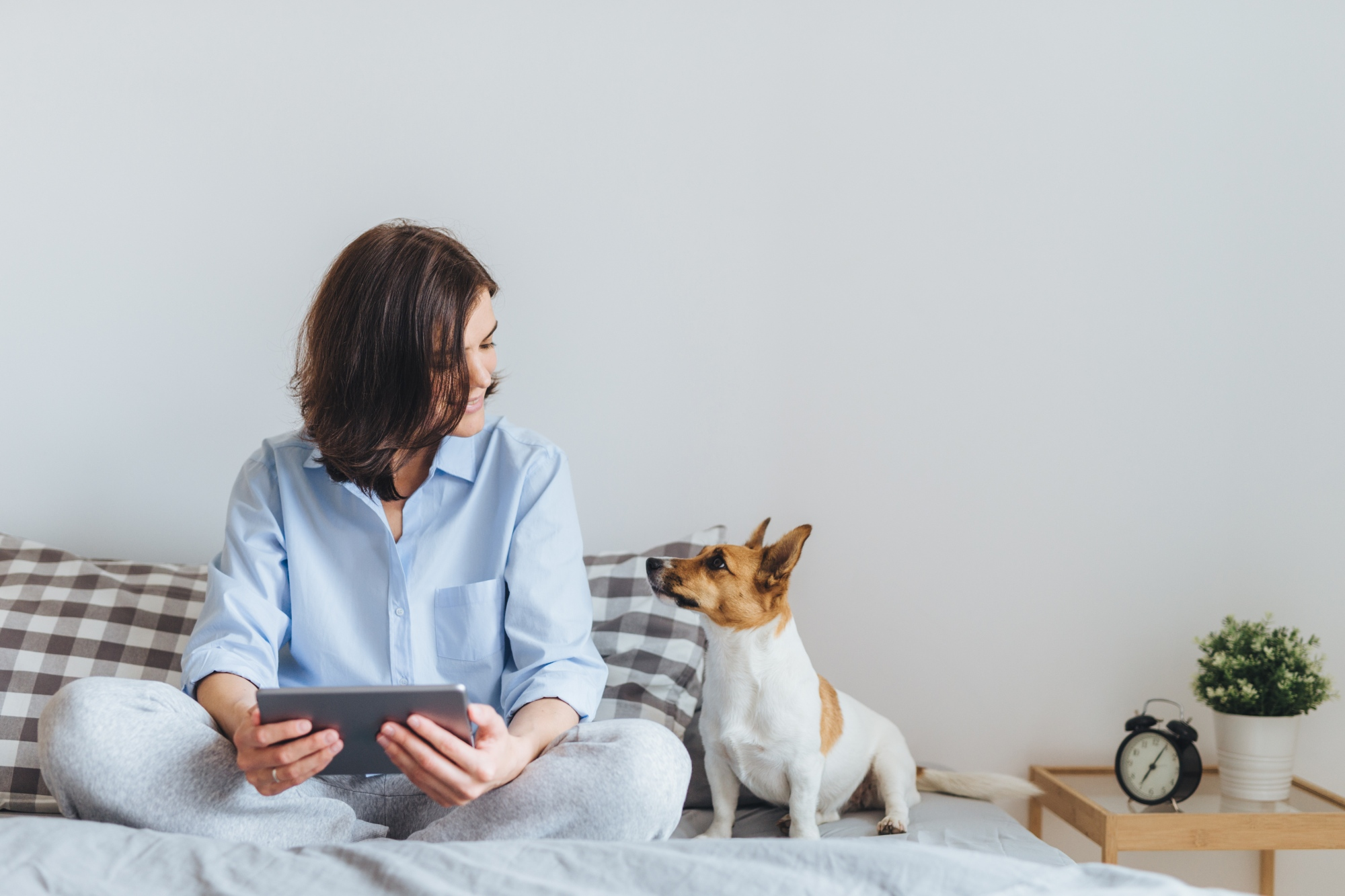 Woman with tablet, sitting on bed with dog